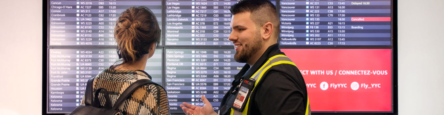 Photo of man and woman looking at flight information display board